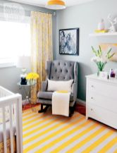 a-small-nursery-with-grey-walls-white-and-grey-furniture-a-dresser-an-open-shelf-a-printed-rug-and-curtains-a-yellow-pendant-lamp