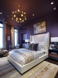 a-sophisticated-bedroom-with-deep-purple-walls-a-white-bed-stained-furniture-sunburst-chandeliers-and-some-artworks