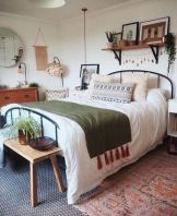 a-spring-boho-bedroom-in-neutrals-with-a-metal-bed-wooden-furniture-macrame-potted-greenery-and-printed-bedding