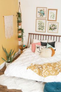 a-spring-boho-bedroom-with-a-yellow-statement-wall-printed-bedding-a-floral-gallery-wall-and-potted-plants