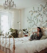 a-spring-boho-bedroom-with-neutral-walls-a-neutral-metal-bed-a-white-chandelier-a-painted-tree-potted-greenery