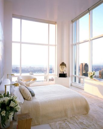 a-stunning-neutral-bedroom-with-some-cabinets-a-bed-tree-stumps-a-bet-chair-and-glass-walls-with-the-views-of-a-big-city