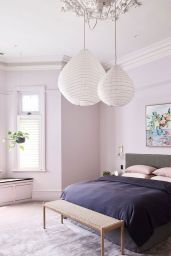 a-stylish-contemporary-bedroom-with-blush-walls-a-grey-bed-paper-pendant-lamps-and-pink-and-deep-purple-bedding