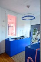 a-super-bold-blue-yet-small-kitchen-with-not-many-cabinets-a-statement-artwork-and-a-bright-blue-chandelier