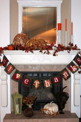 a-vintage-Thanksgiving-mantel-with-bold-leaves-pumpkins-of-porcelain-and-lights-a-fabric-garland-and-orange-candles