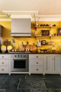 a-vintage-kitchen-with-grey-cabinetry-black-countertops-a-yellow-accent-wall-and-open-shelves-with-pretty-artworks