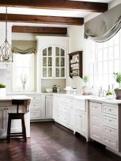 a-vintage-white-kitchen-with-elegant-cabinetry-dark-wooden-beams-and-sotols-that-add-interest-grey-and-green-curtains