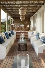 a-welcoming-beach-patio-with-white-benches-blue-pillows-pendant-wicker-lamps-and-a-dining-set-of-wood