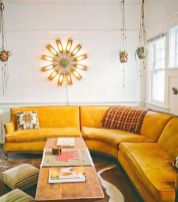 a-welcoming-boho-living-room-with-a-curved-honey-yellow-sofa-a-wooden-table-striped-stools-a-sunburst-lamp-and-hanging-plants