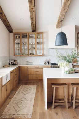 a-welcoming-modern-farmhouse-kitchen-with-light-colored-cabinets-wooden-beams-and-stools-that-warm-up-the-space