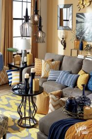 a-whimsical-living-room-with-yellow-walls-grye-furniture-blue-and-yellow-pillows-and-blankets-pendant-lamps-and-a-coffee-table-plus-touches-of-navy