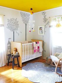 a-whimsy-nursery-with-a-yellow-ceiling-simple-furniture-painted-walls-a-blue-rug-bold-textiles-and-toys