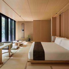 a-zen-bedroom-with-low-wooden-furniture-wooden-screens-a-glazed-wall-and-some-statement-plants-and-artworks