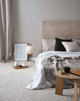 a-zen-like-bedroom-in-neutrals-with-a-woven-headboard-neutral-bedding-a-low-wooen-table-and-some-trays-plus-a-floor-lamp