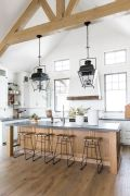 an-airy-and-chic-white-kitchen-with-a-wooden-kitchen-island-and-wooden-beams-on-the-ceiling-plus-refined-vintage-lamps-on-them