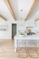an-airy-white-kitchen-with-an-elegant-kitchen-island-copper-stools-light-colored-wooden-beams-that-add-warmth-to-the-space