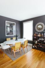 an-elegant-grey-and-yellow-dining-room-with-graphite-grey-walls-an-oval-marble-table-yellow-chairs-a-dark-home-bar-and-a-sunburst-mirror