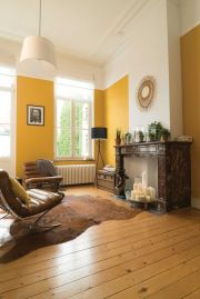 an-elegant-living-room-with-yellow-walls-a-fireplace-with-candles-leather-chairs-and-potted-plants-on-the-mantel