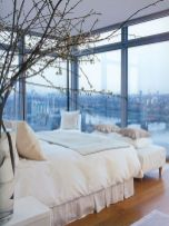 an-elegant-modern-bedroom-with-a-bed-an-upholstered-bench-some-nightstands-and-glass-walls-to-enjoy-the-views-of-the-city