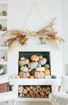 heirloom-pumpkins-stacked-in-the-fireplace-a-dried-grass-overhead-installation-and-some-firewood-for-fall-and-Thanksgiving