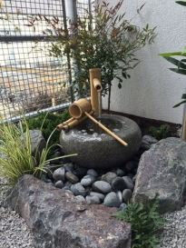 rocks-pebbles-a-traditional-stone-and-bamboo-fountain-greenery-in-between-the-rocks-compose-a-small-and-lovely-front-yard