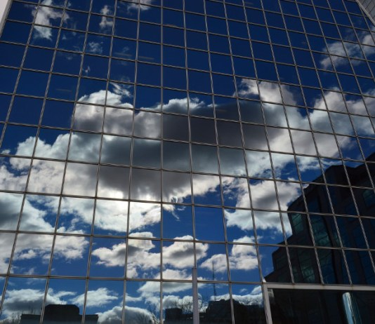 A skyscraper with reflection of clouds