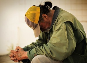 Homeless man sitting against wall with hands folded and head down.