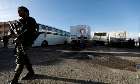 A Syrian soldier secures aid convoy after its return from eastern Ghouta in Damascus