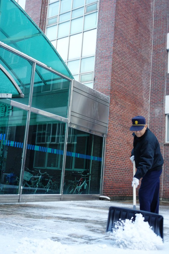 Kangnam University security guard Uhm Jae-joon (69) clears a path in front of Shim Jeon Hall, Building 2. (Photo: Charles Ian Chun)