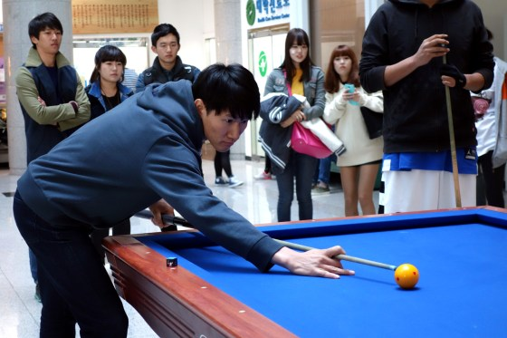 Kim Sang-eon attempts a tricky shot as other students look on. (Photo: Charles Ian Chun)