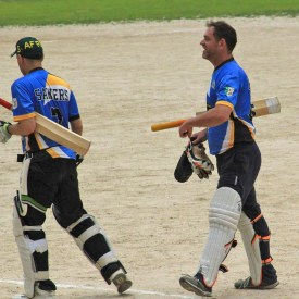The writer (right) and his cricket teammate walk off the field. (Photo: Kristen Sawyers)