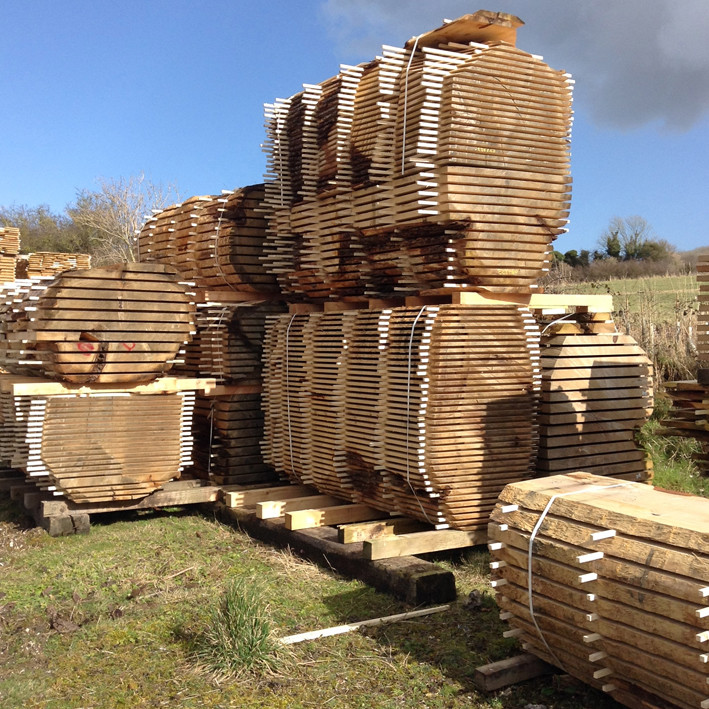 english cedar of lebanon boules stacked in the yard at cocking sawmills
