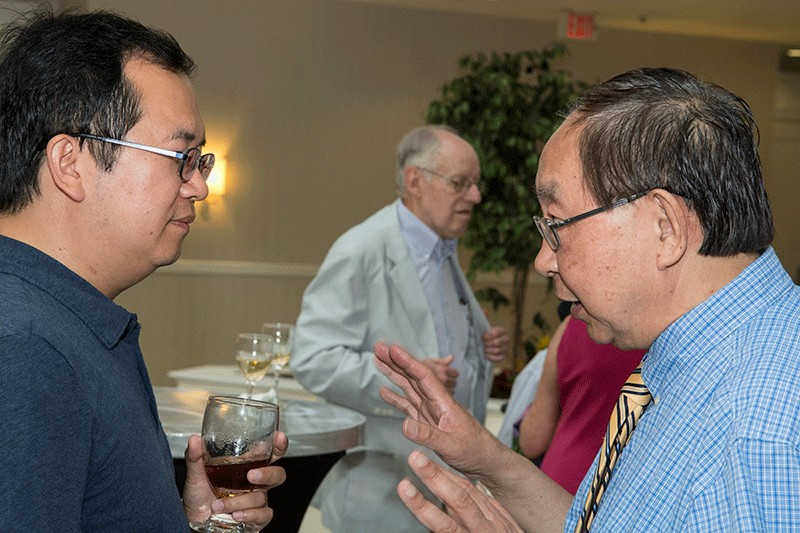 At a 2016 reception, Dr. Gao chats with Xiaoming Li, associate professor in the department. Stanley Sandler, H.B. du Pont Professor Emeritus, can be seen in the background.