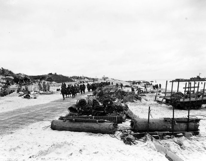 Scene_on_Utah_Beach_with_troops_marching_up_the_road_9_June_1944