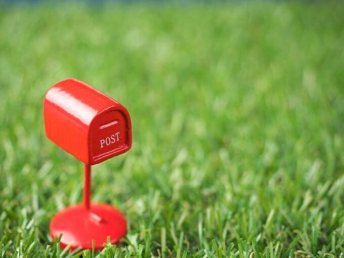 芝生に赤い小さなおもちゃのポスト