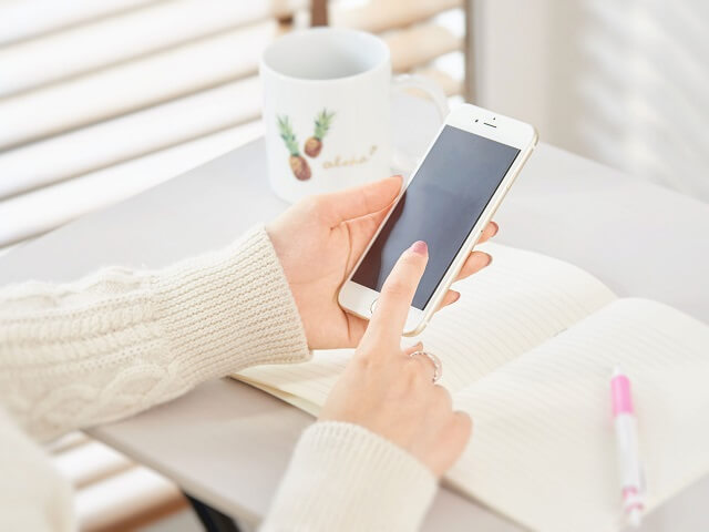 スマートフォンをタッチする女性の手