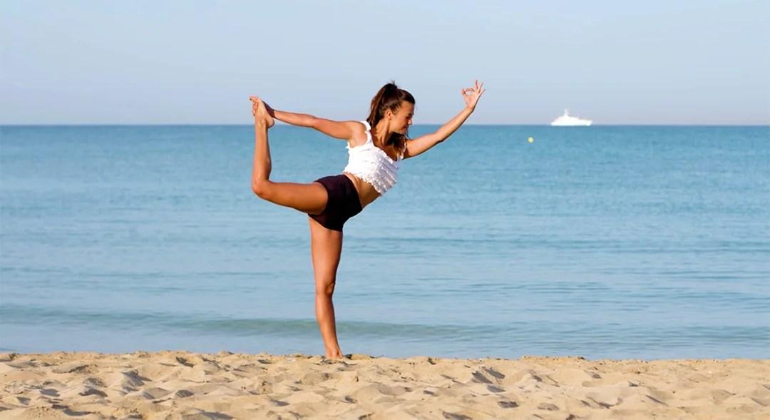 Practicando yoga en Playa de Palma según el post 4 formas divertidas de ejercitarse al aire libre de Enjoy Restaurants