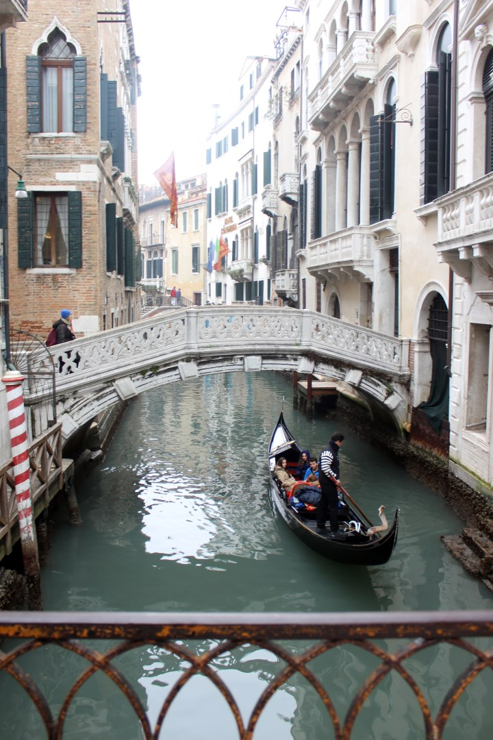 Gondola passing under bridge on the Grand Canal in Venice Italy