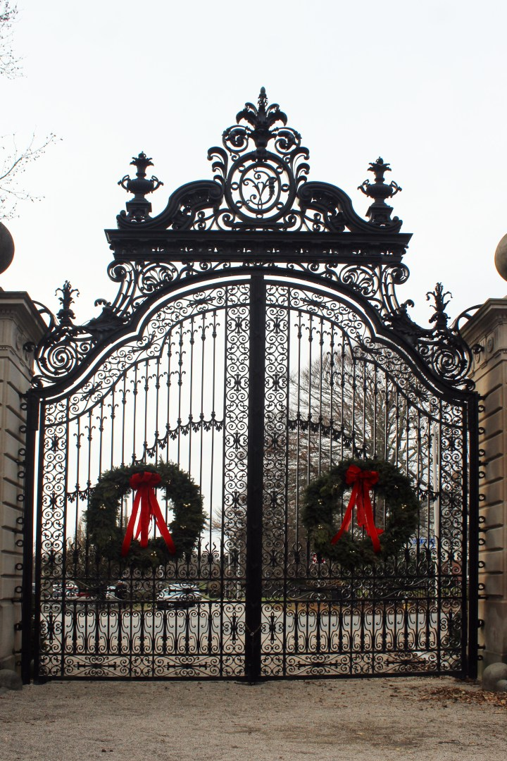 The Breakers - Newport RI | The wrought iron gates welcoming guests to The Breakers are tastefully decorated with wreaths for the holiday season. The gates, weighing 5,000 pounds each, are works of art in themselves, topped by an ornate crown piece. They were recently restored to their original grandeur.