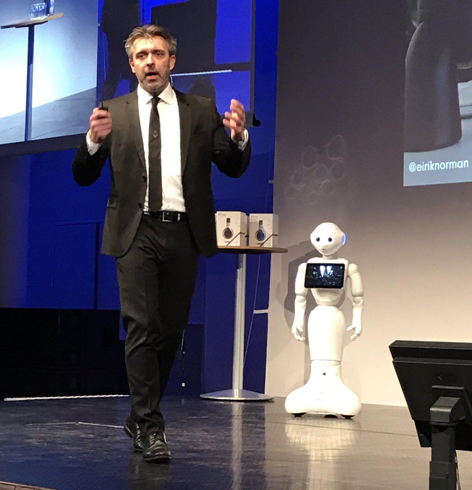 0cefb703 Eirik på scenen på Oslo Business Forum i sort dress, hvit skjorte og sort  slips. Sammen med den ikke fullt så velkledde roboten Pepper.