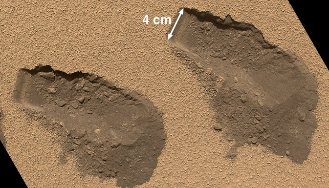 Toma del rover Curiosity recogiendo muestras en Marte