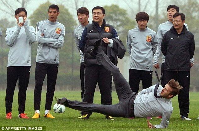 (Foto: Daily Mail) David Beckham pierde el equilibrio y cae ante jóvenes futbolistas Chinos
