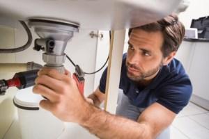 plumber repairing leak under kitchen sink