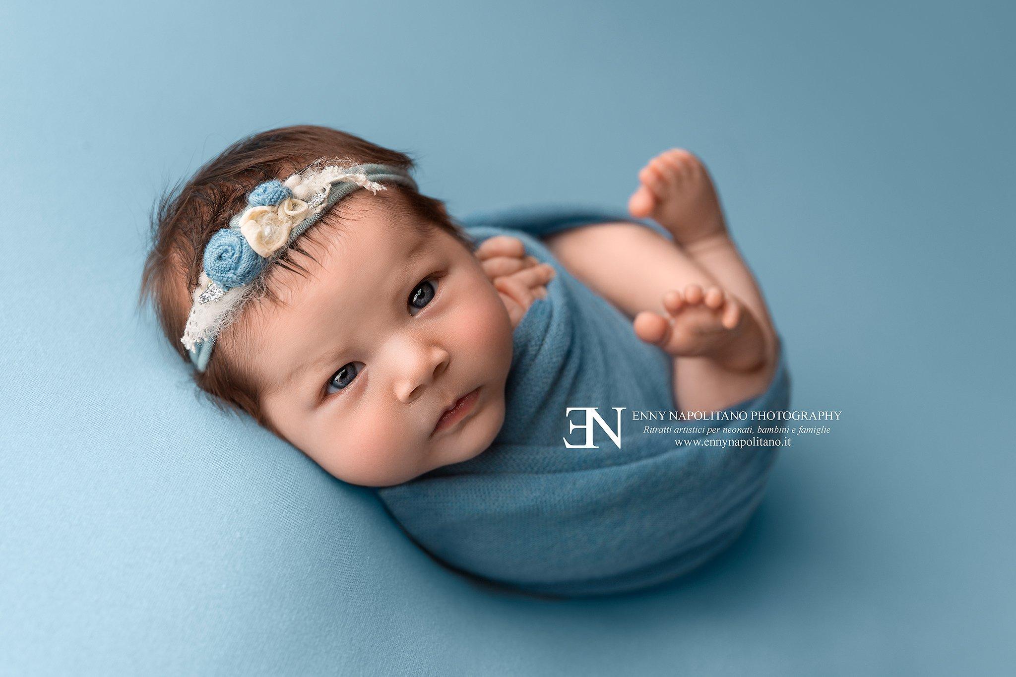 fotografia di una neonata sveglia e fasciata durante un servizio fotografico per neonati