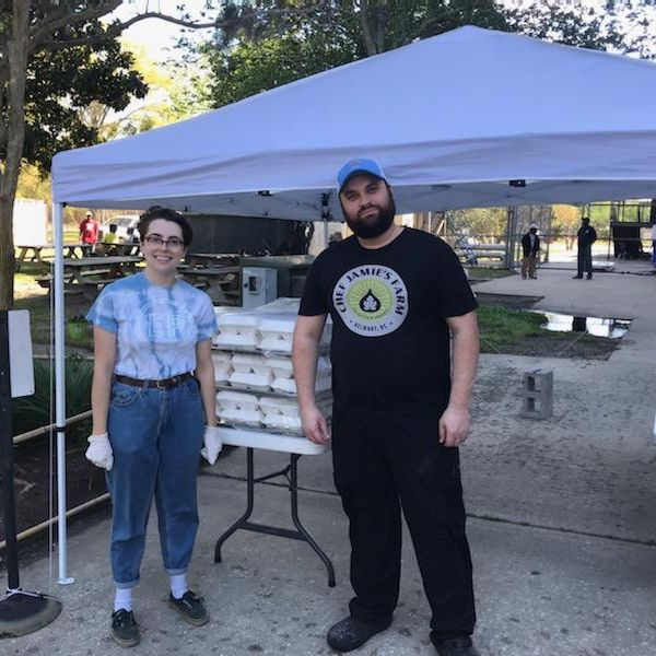 Bianca, Community Manager at Enough Pie, stands with a 5Church employee who delivered ~200 boxed lunches for residents at Joseph Floyd Manor.