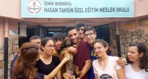 öğrenciler okul tabelası önünde kepçe köpekle beraber toplu poz veriyorlar