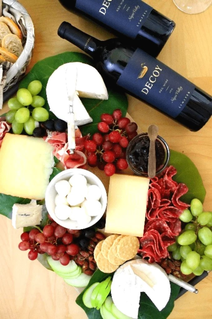 Display of cheeses and fruit, nuts and crackers on a cheeseboard, plus two bottles of fine