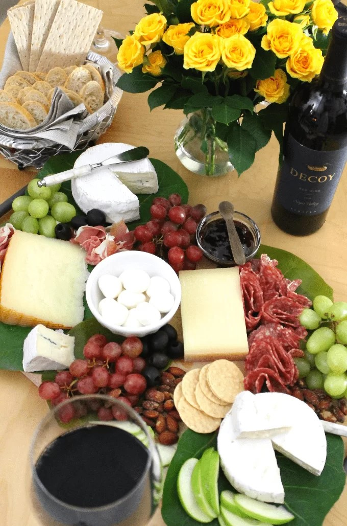 cheese board with charcuterie, grapes and crackers