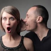 man telling a secret to shocked woman