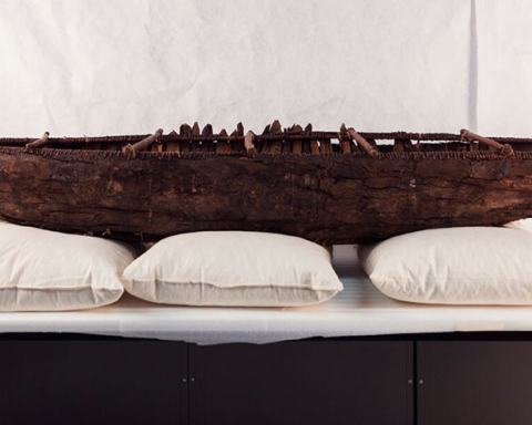 model of ancestral yagan canoe on table in museum storage room